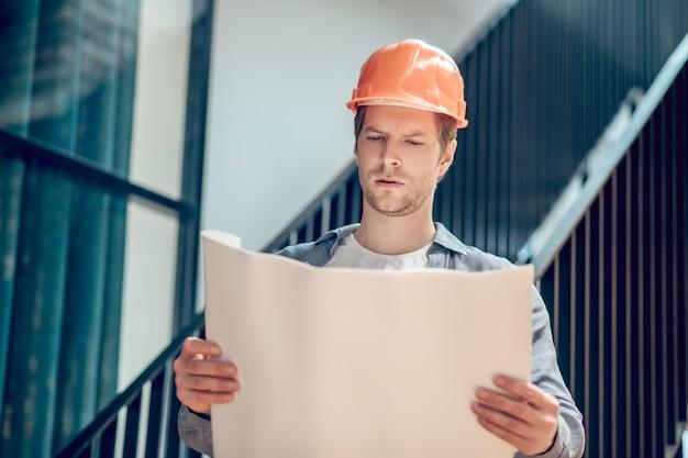 Arbeitserfahrung. konzentrierter mann in orangefarbenem schutzhelm, der sich den bauplan auf dem auf der baustelle stehenden papier genau ansieht