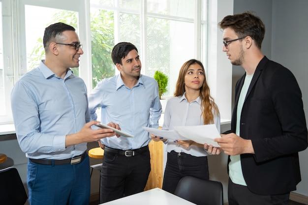 Arbeitsgruppe mit drei mitarbeitern, die einem ernsthaften jungen teamleiter bericht erstatten