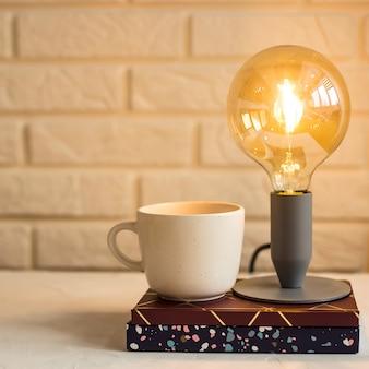 Arbeitshefte und segelflugzeuge auf dem desktop, auf denen sich eine lampe und eine tasse kaffee befinden
