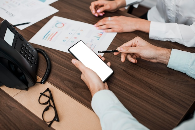 Arbeitskollegen, die an mobiltelefonen und grafiken arbeiten