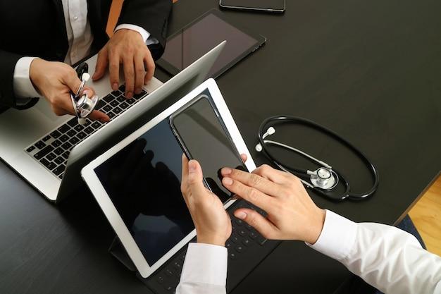 Arbeitskonzept der medizinischen co, doktor, der mit intelligentem telefon und digitaler tablette und laptop-computer arbeitet