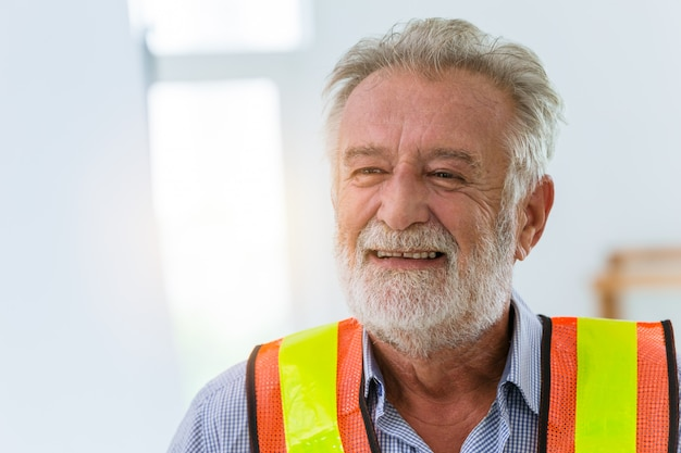 Arbeitskonzept des glücklichen freundlichen lächelnglücks der älteren ingenieurarbeitskraft.