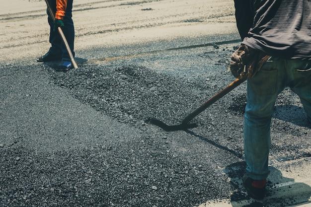 Arbeitskräfte auf asphaltierender straßenbetoniermaschinenmaschine während der straßenstraße, die arbeiten repariert