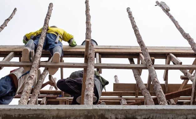 Arbeitskräfte, die auf hölzernem baugerüst im neubau stehen