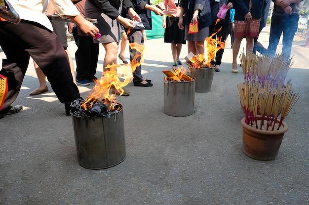 Arbeitskräfte, die gefälschtes papiergeld auf chinesischem neujahrsfest brennen