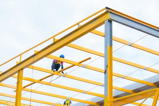 Arbeitskräfte, die gelbe farbmetallstruktur auf die dachoberseite malen