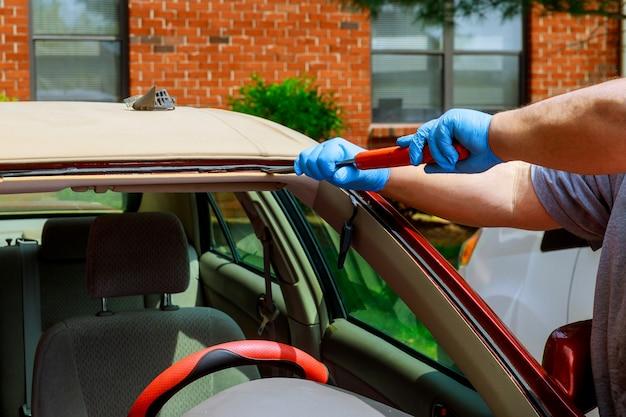 Arbeitskräfte, die glasierende windschutzscheibe auf einem auto eines autoservices entfernen