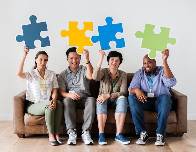 Arbeitskräfte, die puzzlespielikonen sitzen und halten
