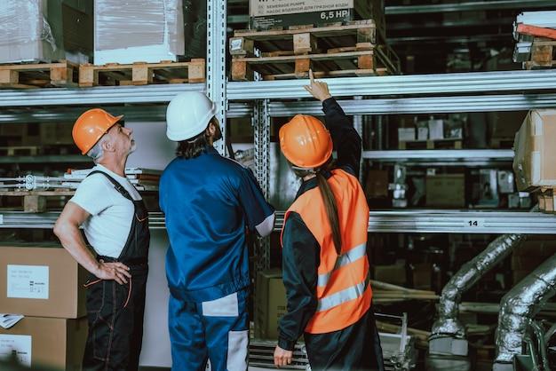 Arbeitskräfte, die uniform und schutzhelme im lager tragen