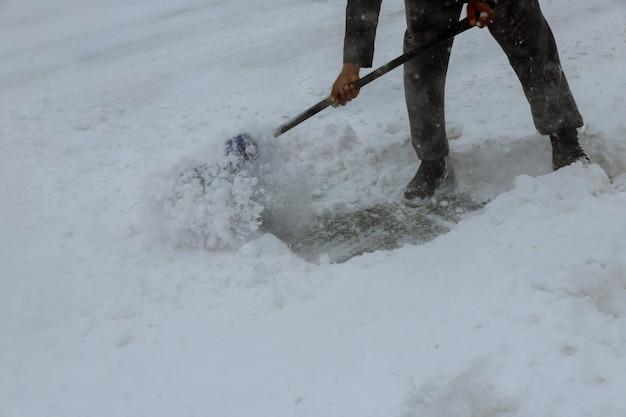 Arbeitskräfte fegen schnee von der straße im winter und säubern straße vom schneesturm.