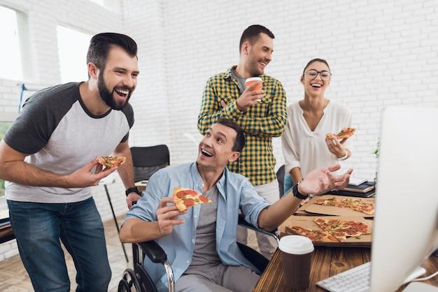 Arbeitskräfte und mann im rollstuhl betrachten computer und lachen.