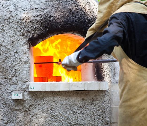 Arbeitskräfte während der glasverarbeitung - heiß schmelzende gläser