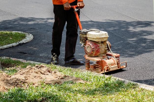 Arbeitskraft benutzt den vibrierenden plattenverdichter, der asphalt bei der straßenreparatur verdichtet