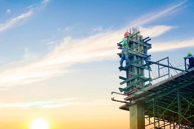 Arbeitskraft, die an gebäude vom hochland und von der stahlstange an der baustelle steht und arbeitet.