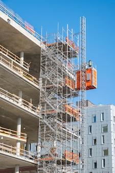 Arbeitskraft, die an struktur des baugerüsts arbeitet
