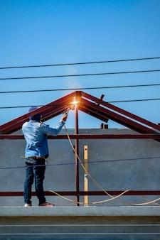 Arbeitskraft, die auf dachspitze steht und struktur des hauses in der baustelle schweißt