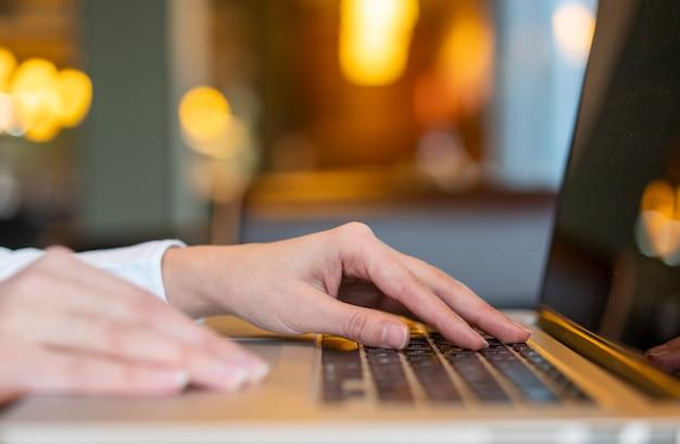 Arbeitskraft, die auf laptop mit bokeh schreibt