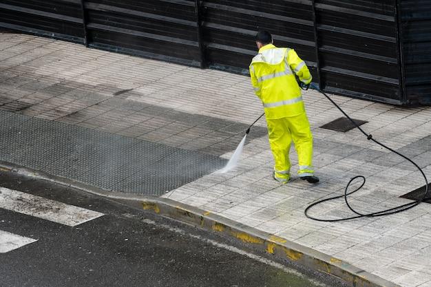Arbeitskraft, die den bürgersteig mit druckwasser säubert. wartungs- oder reinigungskonzept