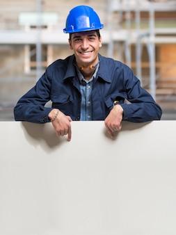 Arbeitskraft, die ein weißes zeichen in einer baustelle zeigt