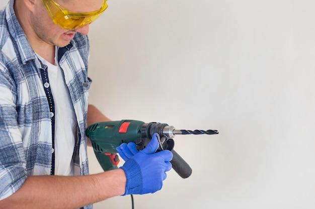 Arbeitskraft, die einen bohrhammer hält