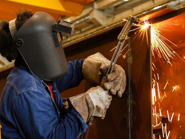 Arbeitskraft, die fackelschneider verwendet, um metall zu schneiden