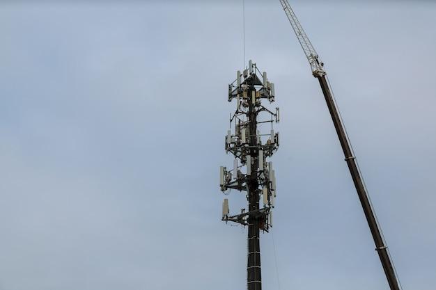 Arbeitskraft, die karabiner-geschirr zur sicherheit auf antennenmast klammert