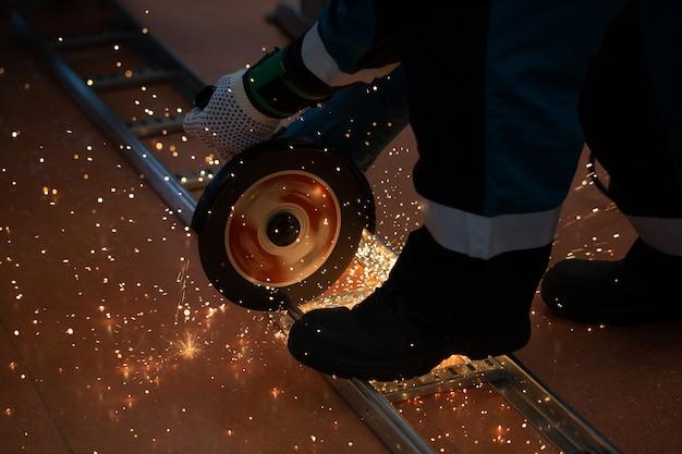 Arbeitskraft, die metall mit einer säge sägt