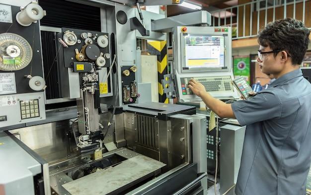 Arbeitskraft, die mit cnc-maschine an der werkstatt arbeitet