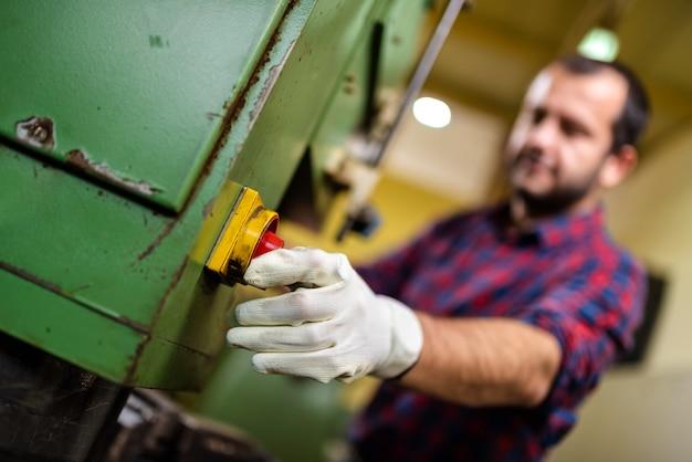 Arbeitskraft, die netzschalter auf einer industriemaschine dreht