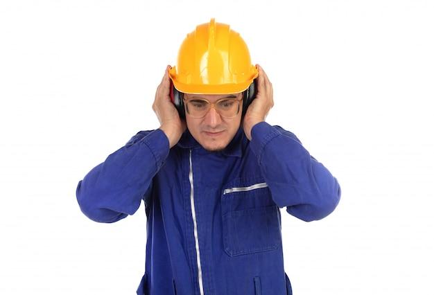 Arbeitskraft, die seine ohren mit gelbem sturzhelm bedeckt