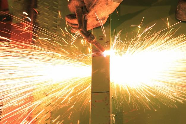 Arbeitskraft, die stahlstange unter verwendung der metallfackel schneidet