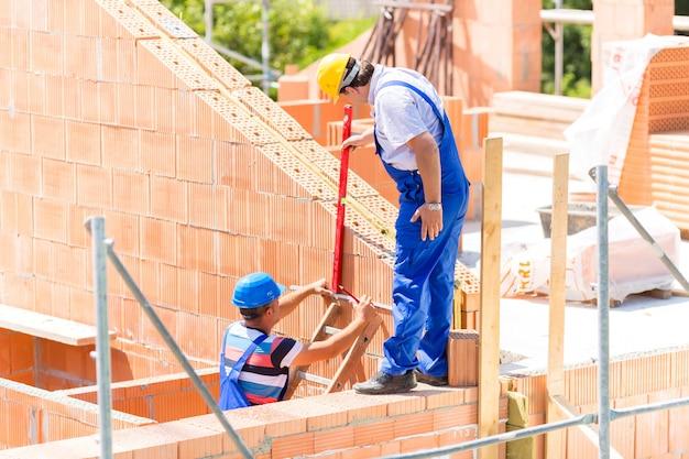 Arbeitskraft, die wände auf baustelle überprüft