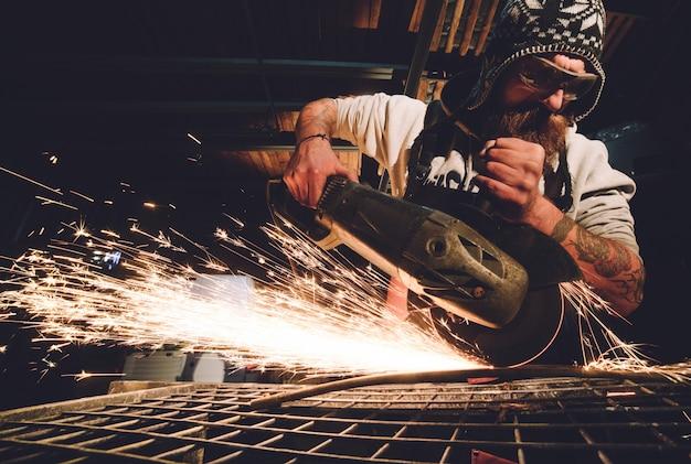 Arbeitskraft, die winkelschleifer in der fabrik verwendet und funken wirft