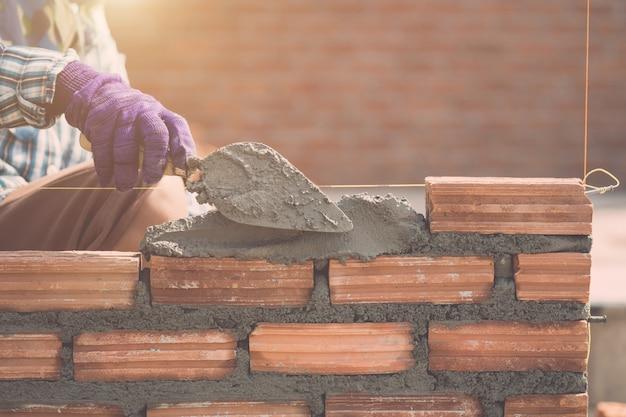 Arbeitskraft, die ziegelsteinwand im prozess des wohnungsbaus installiert
