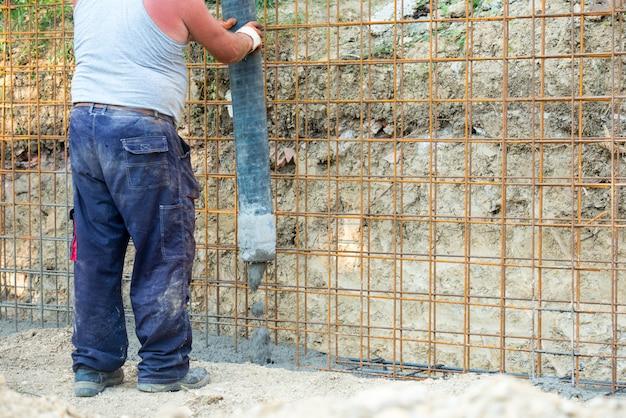 Arbeitskraft, die zu hause betonmischung der mischung gießt