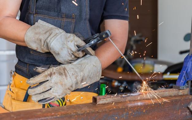 Arbeitskraft in der arbeitskleidung, die das stahlteil durch handbuch mit sicherheitsausrüstung schweißt