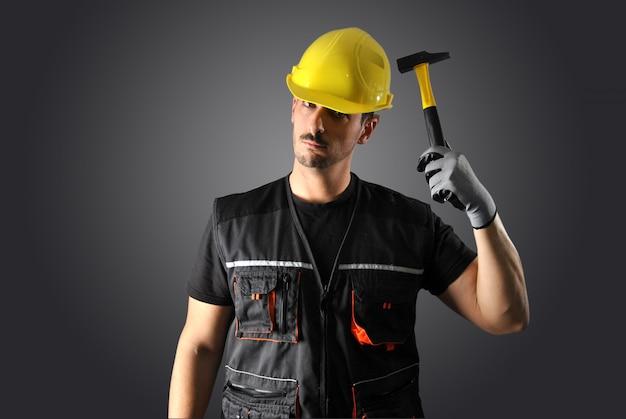 Arbeitskraft mit gelbem sturzhelm, bohrgerät und hammer