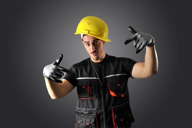 Arbeitskraft mit gelbem sturzhelm und gesicht verrückt
