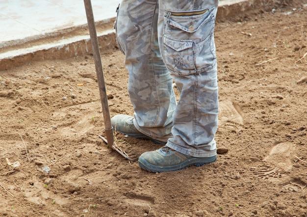 Arbeitskraft mit rührstange beim zerquetschen des bodens im yard