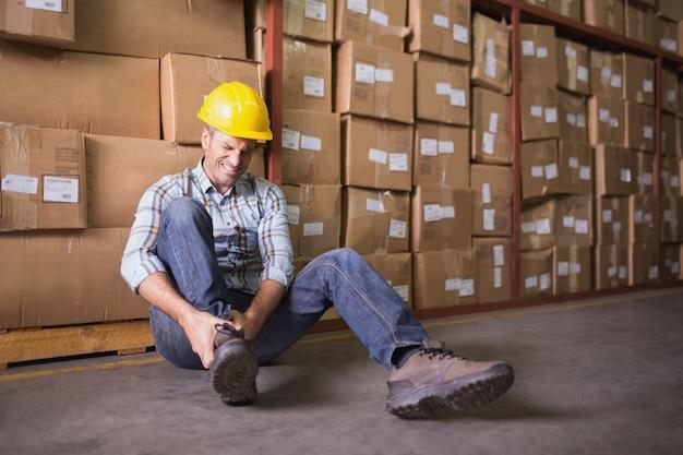 Arbeitskraft mit verstauchtem knöchel auf boden im lager