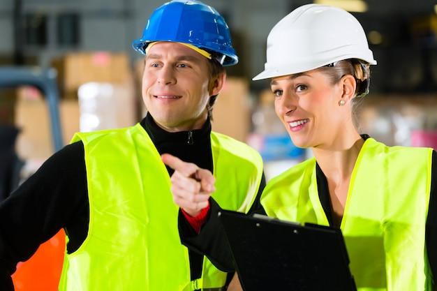 Arbeitskraft oder lagerverwalter und sein mitarbeiter mit klemmbrett am lager der spedition, zeigend