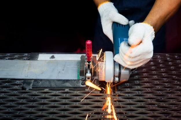 Arbeitskraftausschnitt mit schleifer und schweißensmetall mit vielen scharfen funken in der fabrik