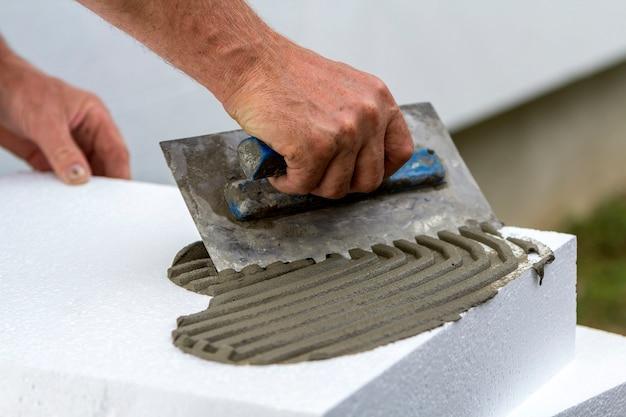 Arbeitskrafthand mit der kelle, die kleber auf polyurethanschaumblatt für hausisolierung aufträgt.