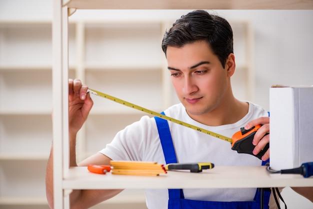 Arbeitskraftmann, der zusammenbauendes bücherregal repariert