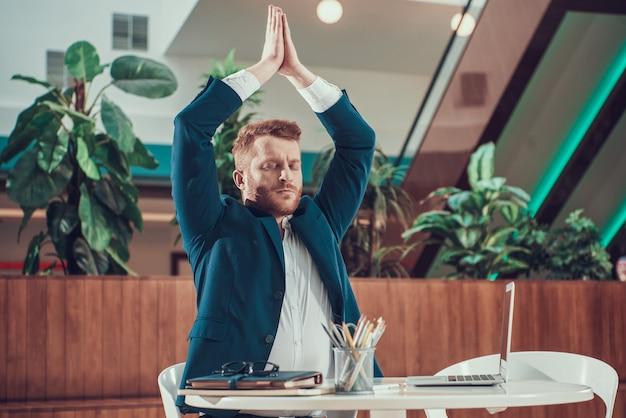 Arbeitskraftmann in der klage meditierend am schreibtisch im büro.