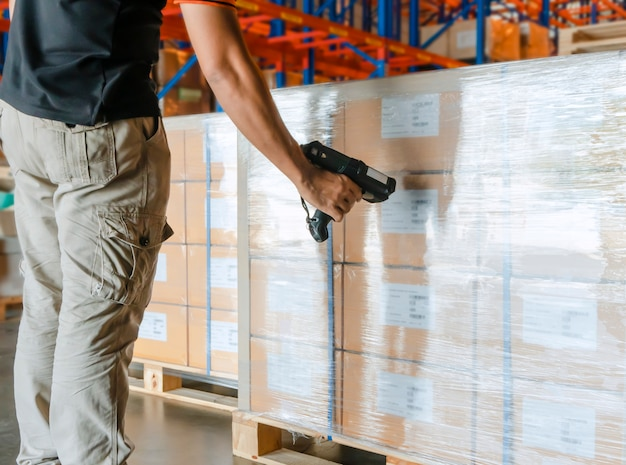 Arbeitskraftmannhand, die strichkodescanner mit dem scannen auf frachtpalette am lager hält