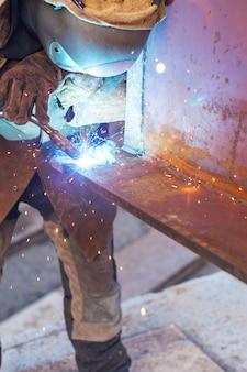 Arbeitskraftschweißen in einer fabrik. schweißen an einer industrieanlage