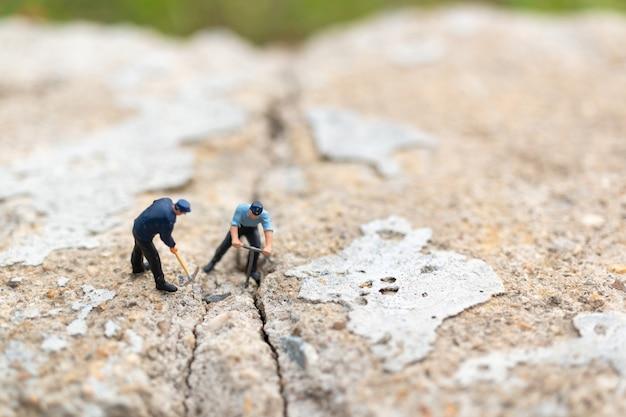 Arbeitskraftteam, das an beton mit gebrochenem arbeitet