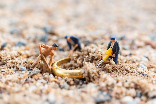 Arbeitskraftteam, das goldringe auf dem boden gräbt