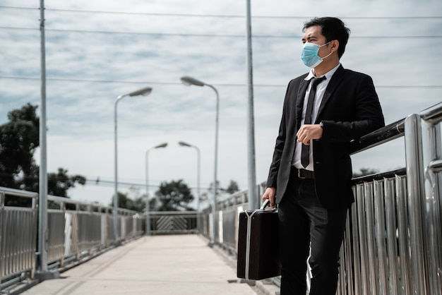 Arbeitslose gestresste junge asiatische geschäftsmann tragen maske tragen eine arbeitstasche, die nach arbeit im anzug bedeckt gesicht sucht